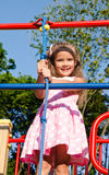 Smiling little girl playing on playground equipment Royalty Free Stock Photos