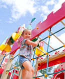 Smiling little girl playing on playground equipment Stock Image