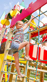 Smiling little girl playing on playground equipment Royalty Free Stock Image