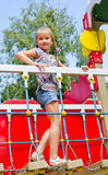 Smiling little girl playing on playground equipment Stock Photography