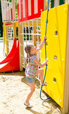 Smiling little girl playing on playground equipment Stock Photo