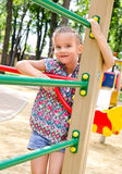Smiling little girl playing on playground equipment Stock Images