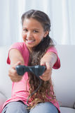 Smiling little girl playing video game on sofa Stock Images