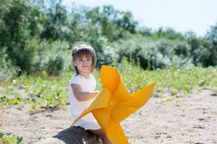 Smiling little girl playing with windmill Stock Photo