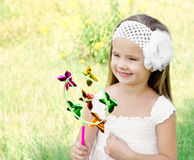 Smiling little girl playing with windmill toy Royalty Free Stock Photography