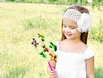 Smiling little girl playing with windmill toy Royalty Free Stock Photos