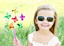 Smiling little girl playing with windmill toy Royalty Free Stock Photo