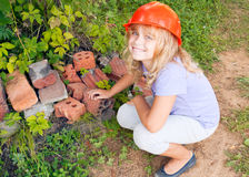 Smiling little girl plays as a construction worker Stock Image