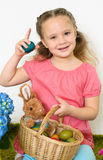 Smiling little girl plays with a basket of Easter eggs. Lovely little girl in Easter scene Royalty Free Stock Image