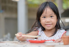 Smiling little girl plays cook on the table Stock Image