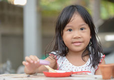 Smiling little girl plays cook on the table Royalty Free Stock Image