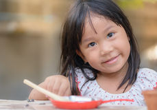 Smiling little girl plays cook on the table stock images