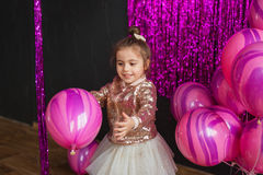 Smiling little girl plays with pink balloons at studio Stock Photography