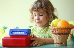 Smiling little girl plays shop Stock Photo