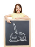 Smiling little girl pointing finger to blackboard Royalty Free Stock Photography