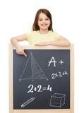 Smiling little girl pointing finger to blackboard Stock Photos