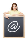 Smiling little girl pointing finger to blackboard Royalty Free Stock Photos