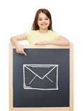 Smiling little girl pointing finger to blackboard Stock Image