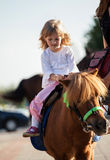 Smiling little girl  on a pony Royalty Free Stock Images