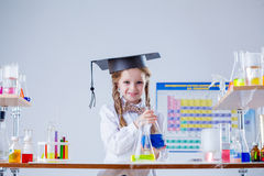 Smiling little girl posing in graduate hat at lab Stock Photo
