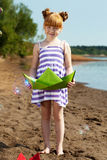 Smiling little girl posing with green paper boat Royalty Free Stock Images