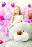 Smiling little girl posing with plush bear Royalty Free Stock Photos