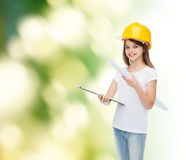 Smiling little girl in protective helmet. Childhood, construction, architecture, building and people concept - smiling little girl in protective helmet with Stock Photography