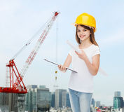 Smiling little girl in protective helmet. Childhood, construction, architecture, building and people concept - smiling little girl in protective helmet with Royalty Free Stock Photo