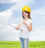 Smiling little girl in protective helmet. Childhood, construction, architecture, building and people concept - smiling little girl in protective helmet with Royalty Free Stock Photography