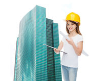 Smiling little girl in protective helmet. Childhood, construction, architecture, building and people concept - smiling little girl in protective helmet with Royalty Free Stock Image
