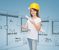 Smiling little girl in protective helmet. Childhood, construction, architecture and people concept - smiling little girl in protective helmet with clipboard and Royalty Free Stock Photography