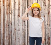 Smiling little girl in protective helmet. Construction and people concept - smiling little girl in protective helmet Royalty Free Stock Photos
