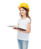 Smiling little girl in protective helmet. Construction and people concept - smiling little girl in protective helmet with clipboard Royalty Free Stock Photo