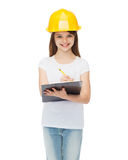 Smiling little girl in protective helmet. Construction and people concept - smiling little girl in protective helmet with clipboard Royalty Free Stock Images