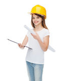 Smiling little girl in protective helmet. Construction and people concept - smiling little girl in protective helmet with clipboard and blueprint Stock Images