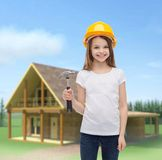 Smiling little girl in protective helmet. Construction and people concept - smiling little girl in protective helmet with hammer Royalty Free Stock Photography