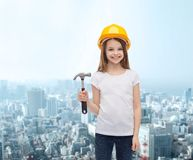 Smiling little girl in protective helmet. Construction and people concept - smiling little girl in protective helmet with hammer Stock Photo