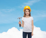 Smiling little girl in protective helmet. Construction and people concept - smiling little girl in protective helmet with hammer Royalty Free Stock Images