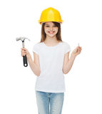 Smiling little girl in protective helmet. Construction and people concept - smiling little girl in protective helmet with hammer and big nail Stock Photography