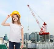 Smiling little girl in protective helmet. Construction and people concept - smiling little girl in protective helmet looking up Royalty Free Stock Photos