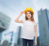 Smiling little girl in protective helmet. Construction and people concept - smiling little girl in protective helmet looking up Stock Photography