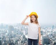 Smiling little girl in protective helmet. Construction and people concept - smiling little girl in protective helmet looking up Stock Photos