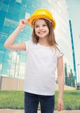 Smiling little girl in protective helmet. Construction and people concept - smiling little girl in protective helmet looking up Stock Image