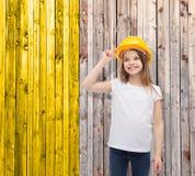 Smiling little girl in protective helmet. Construction and people concept - smiling little girl in protective helmet looking up Stock Images