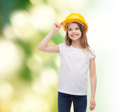 Smiling little girl in protective helmet. Construction and people concept - smiling little girl in protective helmet looking up Stock Photo