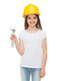 Smiling little girl in protective helmet. Construction and people concept - smiling little girl in protective helmet with wrench Royalty Free Stock Image