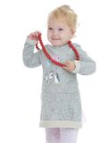 Smiling little girl put on her big red beads Stock Photos