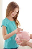 Smiling little girl putting coin into piggy bank Stock Photos