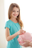 Smiling little girl putting coin into piggy bank Stock Images