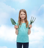 Smiling little girl with rake and scoop Stock Photo